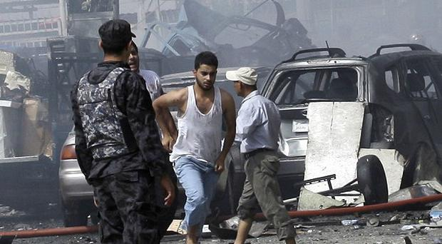 People and security forces gather at the scene of a car bomb explosion in a shopping area in Karradah, Baghdad (AP)