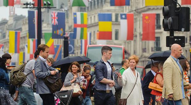 Shoppers walk beneath national flags of the competing Olympic nations as they cross Regent Street, in central London