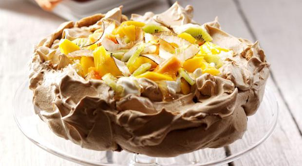 Brown sugar pavlova with|lime and coconut cream topped with tropical fruits