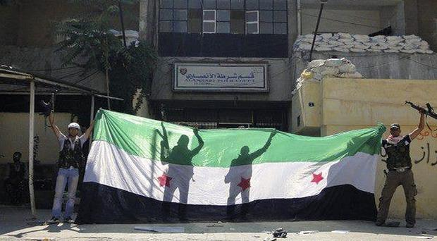 Syrian rebels apparently celebrating after taking over the Ansari police station in the northern city of Aleppo (AP)