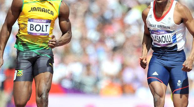 Jamaica's Usain Bolt, left, in action with Great Britain's James Dasaolu, right, in a heat of the men's 100m at The Olympic Stadium, London