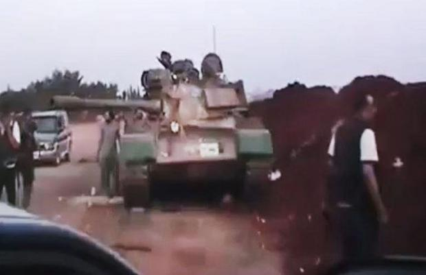 This image made from amateur video released by the Ugarit News and accessed Monday, July 30, 2012, purports to show Free Syrian Army soldiers standing near a military tank in Anadan 16 kilometers (10 miles), from Aleppo, Syria.