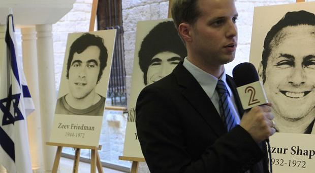 A reporter broadcasts at London's Guildhall in front of pictures of the Israeli team members killed in the 1972 Munich Olympic Games terror attack (AP)