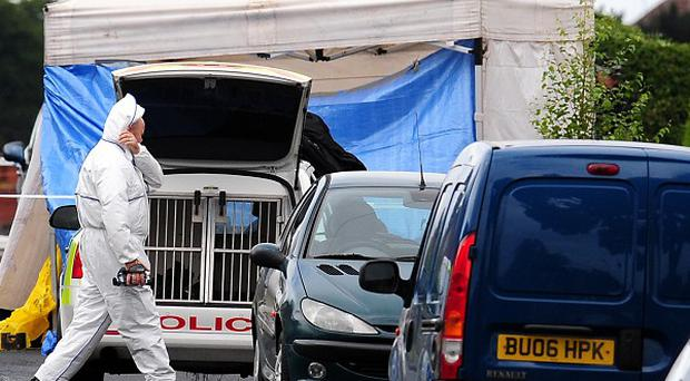 Forensic officers at the scene in Birmingham, where a woman was stabbed to death in a taxi