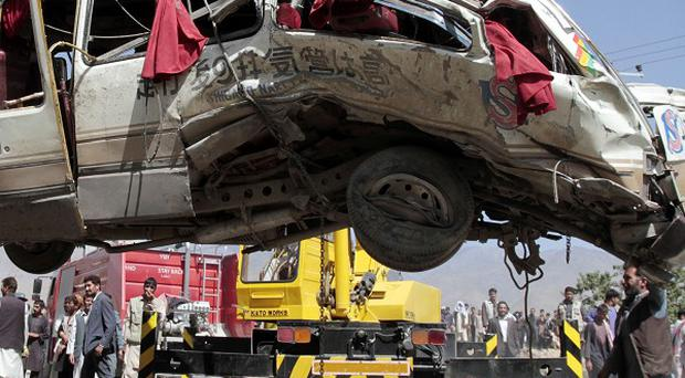 A damaged bus which was hit by a remote control bomb is lifted by a crane on the outskirts of Kabul, Afghanistan (AP)