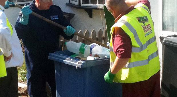 Police officers search through rubbish bins near Tia Sharp's grandmother's home in New Addington, London