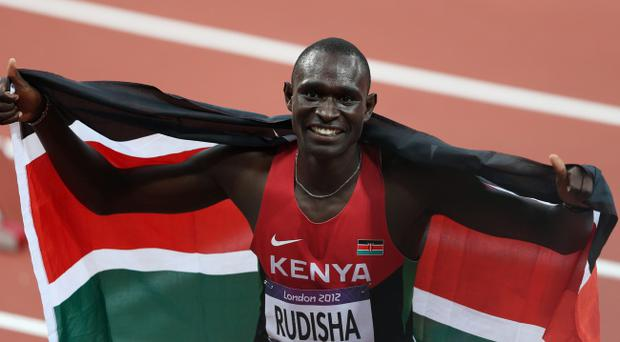 LONDON, ENGLAND - AUGUST 09: David Lekuta Rudisha of Kenya celebrates with his country's national flag after winning gold and setting a new world record of 1.40.91 in the Men's 800m Final on Day 13 of the London 2012 Olympic Games at Olympic Stadium on August 9, 2012 in London, England. (Photo by Clive Brunskill/Getty Images)