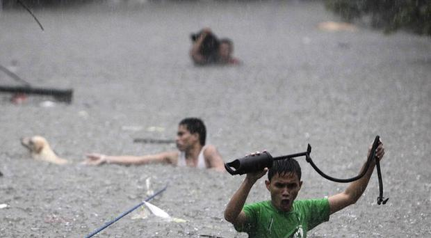 Men crossing deep floodwaters in San Juan, north of Manila, the Philippines (AP)