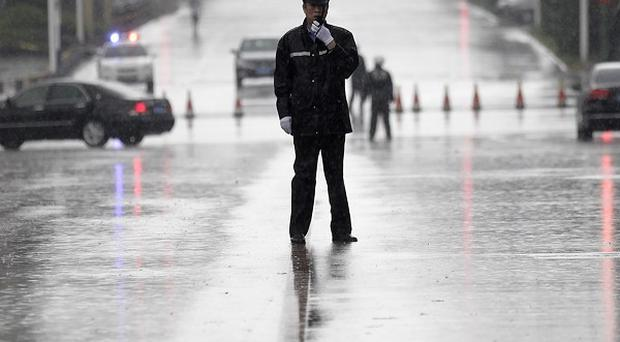 Police officers stand guard at Hefei City Intermediate People's Court where the murder trial of Gu Kailai takes place (AP)