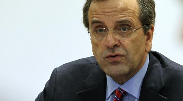 Greek prime minister Antonis Samaras has promised to slash more than 11 billion euro off the country's 2013-14 budget (AP)