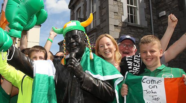 Residents celebrate beside a statue of singer Joe Dolan after watching boxer John Joe Nevin's semi-final on big screens in his home town