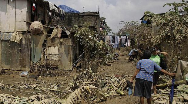 Residents talk beside toppled banana trees as they return to their homes following floodings in the outskirts of Quezon City (AP)