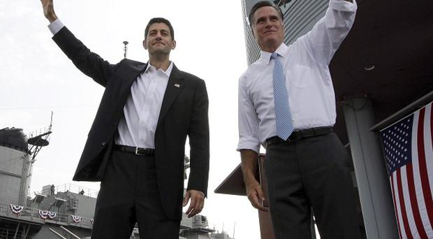 Republican presidential candidate Mitt Romney, right, and vice presidential candidate Paul Ryan wave during a campaign event in Virginia (AP)