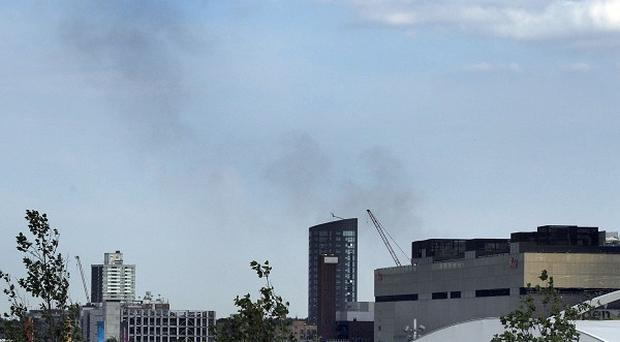 Smoke from a fire at a recycling centre on Chequers Lane in Dagenham, east London is seen in the distance behind the Westfield shopping centre