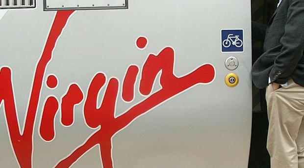 Sir Richard Branson boarding a Virgin train as he could lose his West Coast rail franchise this week
