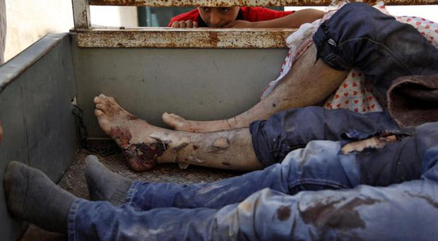 A Syrian boy looks at the bodies of nine Syrians on a truck after they were found dead in an open field and taken to the town of Anadan outskirts of Aleppo, Syria, Monday, Aug. 6, 2012. (AP Photo/Khalil Hamra)