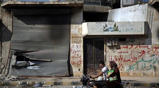 In this Sunday, Aug. 5, 2012 photograph, Syrians on a motorcycle pass by a destroyed shop in town of Atareb outskirts of Aleppo, Syria. (AP Photo/Khalil Hamra)