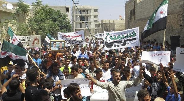 Protesters in the village of Sarmin in Idlib province, Syria (AP)