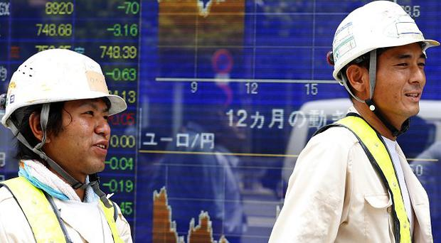 Workers walk past an electronic stock indicator in Tokyo (AP)