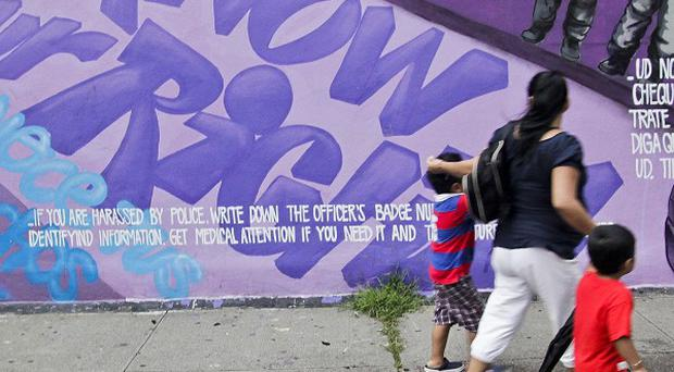 A woman and children walk past a street mural urging people to know their rights if police try to stop and search them in New York (AP)
