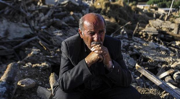 A victim of Saturday's earthquake sits on the ruins of buildings at the village of Bajebaj near the city of Varzaqan in northwestern Iran (AP)