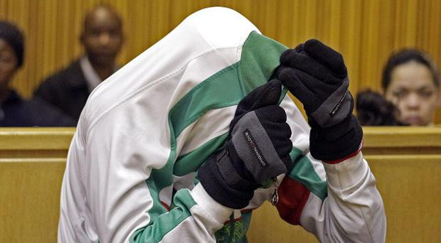 Xolile Mngeni shields his face with his jacket at court in Cape Town, South Africa (AP)