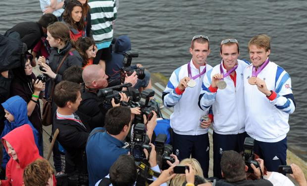 Olympic rower Alan Campbell along with brothers Richard and Peter Chambers are swamped by media and well wishers on their return to the Bann Rowing Club in Coleraine after their medal success in London