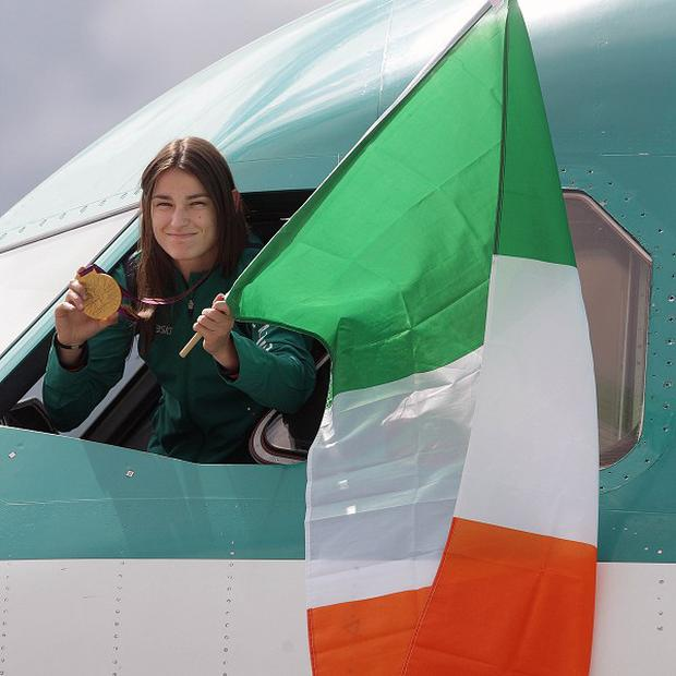 Boxer Katie Tayor holds her Olympic gold medal as she arrives with the rest of the Irish team at Dublin Airport