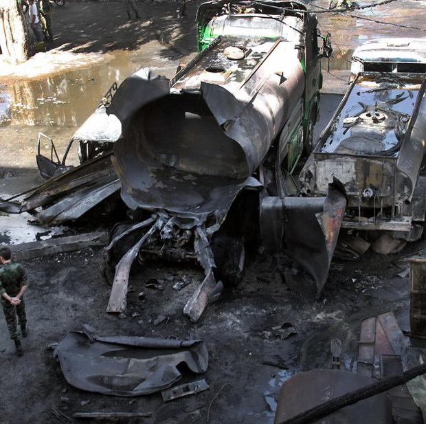 Syrian soldiers investigate the scene after a bomb attached to a fuel truck exploded outside a Damascus hotel in Syria (AP/Sana)