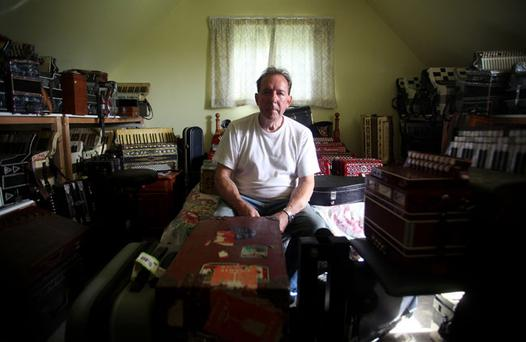 Ken Hopkins who collects, sells and has also written books about accordions pictured at his home in Comber