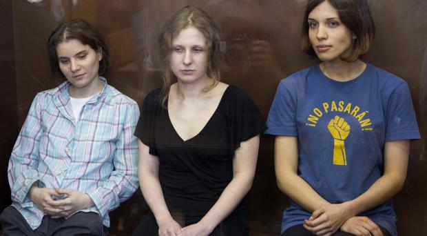 Feminist punk group Pussy Riot members, Nadezhda Tolokonnikova, right, Maria Alekhina, center, and Yekaterina Samutsevich sit in a glass cage at a court room in Moscow, Russia, Friday, Aug. 17, 2012. Security is tight around a Moscow courthouse where three members of the feminist punk band Pussy Riot are to hear the verdict Friday in a trial that could send them to prison for seven years. (AP Photo/Misha Japaridze)
