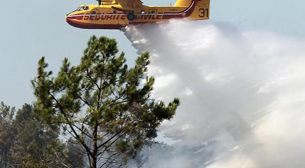 A Canadair plane drops water on a forest fire in Lacanau, south-west France (AP)