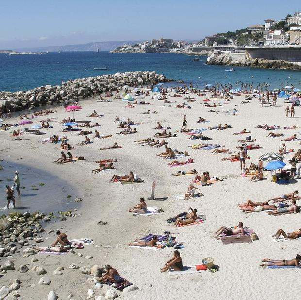 People bathe at the Prophet beach in Marseille, southern France, amid a heatwave alert (AP)