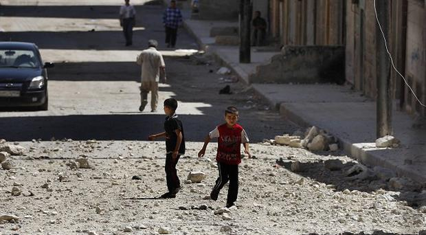 Two Syrian boys play on a street next to a building hit by a government airstrike in Aleppo (AP)