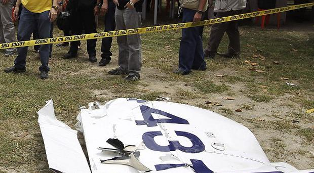 President Benigno Aquino III, third from left, views parts of the plane recovered at the crash site (AP)