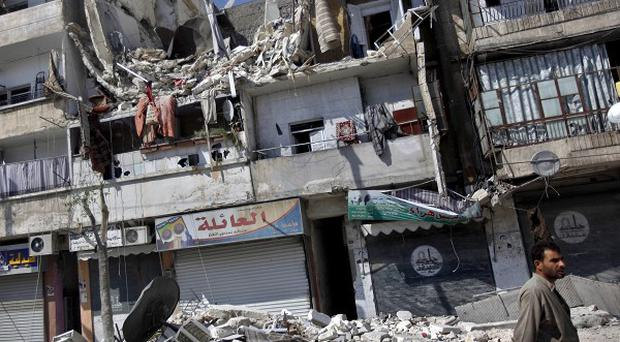 A man walks past a building destroyed by an airstrike in Aleppo (AP)