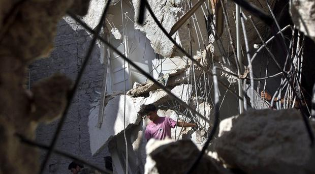 Syrians look for survivors in under the rubble of a building hit by an airstrike in Aleppo (AP)