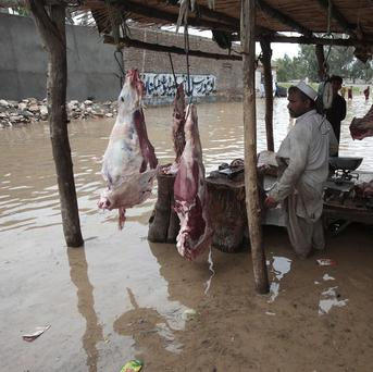 A butcher waits for customers in a flooded street in Nowshera, near Peshawar in Pakistan (AP)