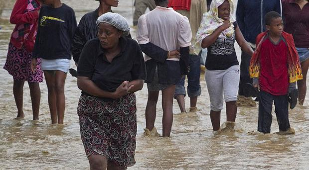 Residents leave their flooded homes in a low-lying area affected by Tropical Storm Isaac in Port-au-Prince, Haiti (AP/Minustah, Logan Abassi)
