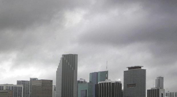 Heavy storm clouds hover over the Miami skyline as Tropical Storm Isaac's weather bands reach the area (AP)