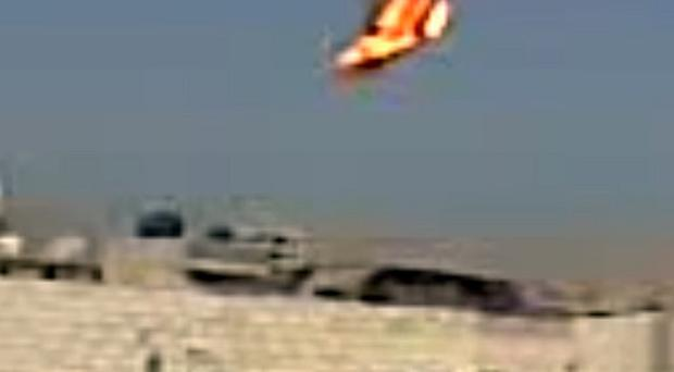 A still from amateur video showing the helicopter falling in flames (AP)