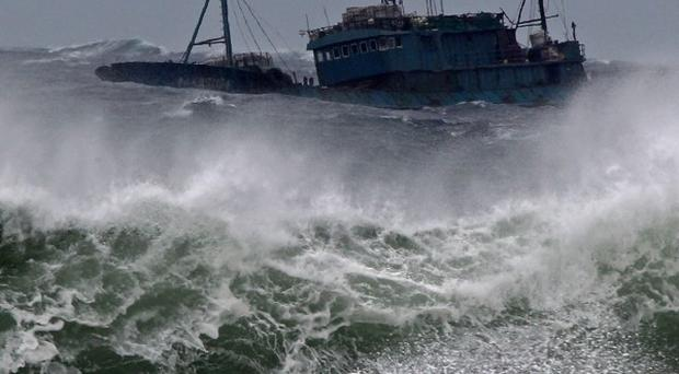 A Chinese fishing boat navigates through rough waves caused by Typhoon Bolaven in waters off Jeju Island, South Korea (AP)