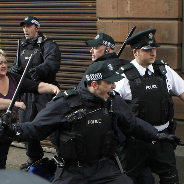 Police officers attempt to stop fighting between loyalist and nationalist groups outside outside St Patrick's Roman Catholic Church in Belfast 2012 (AP)