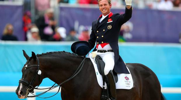 Carl Hester of Great Britain riding Uthopia celebrates after competing in the Team Dressage Grand Prix Special at the London 2012 Olympic Games