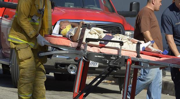 A victim is taken away after a car driven by a 100-year-old hit a group of people outside a South Los Angeles school (AP/Mark J Terrill)