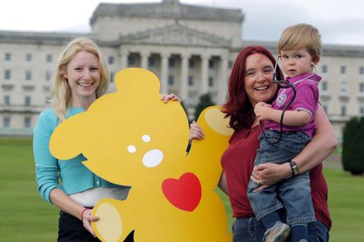 tTwo-year old Liam Clifford and mum Joanne with Children's Heartbeat Trust's Sarah Quinlan at the launch of the Hands Up For Heart Surgery campaign at Stormont