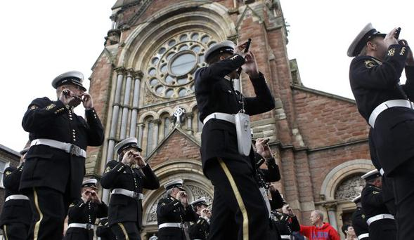A band plays music in contravention of the Parades Commission ruling as it passes by St Patrick's Church in Donegall Street