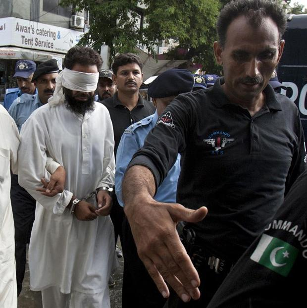 Pakistani police officers escort blindfolded Muslim cleric Khalid Chishti to appear in court in Islamabad (AP)