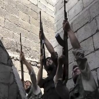 Free Syrian Army fighters raise their weapons during fighting with the Syrian Army (AP)