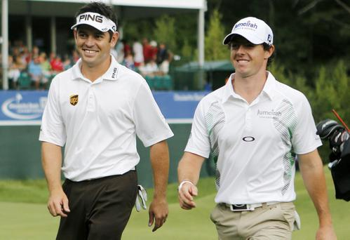 Louis Oosthuizen, left, of South Africa, and Rory McIlroy, of Northern Ireland, leave the 18th green after finishing the third round of the Deutsche Bank Championship PGA golf tournament at TPC Boston in Norton, Mass., Sunday, Sept. 2, 2012. (AP Photo/Michael Dwyer)